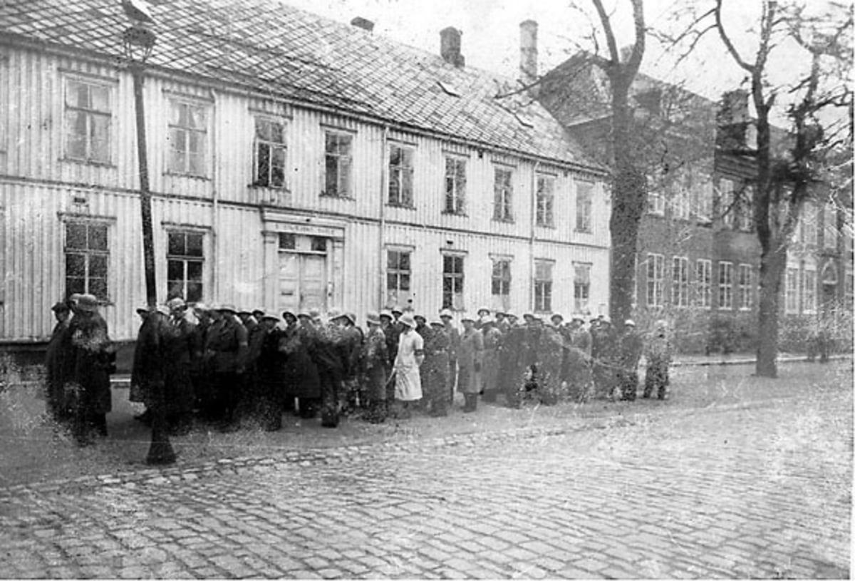Gruppeportrett, flere personer i gata, militære. 2 større bygninger bak.