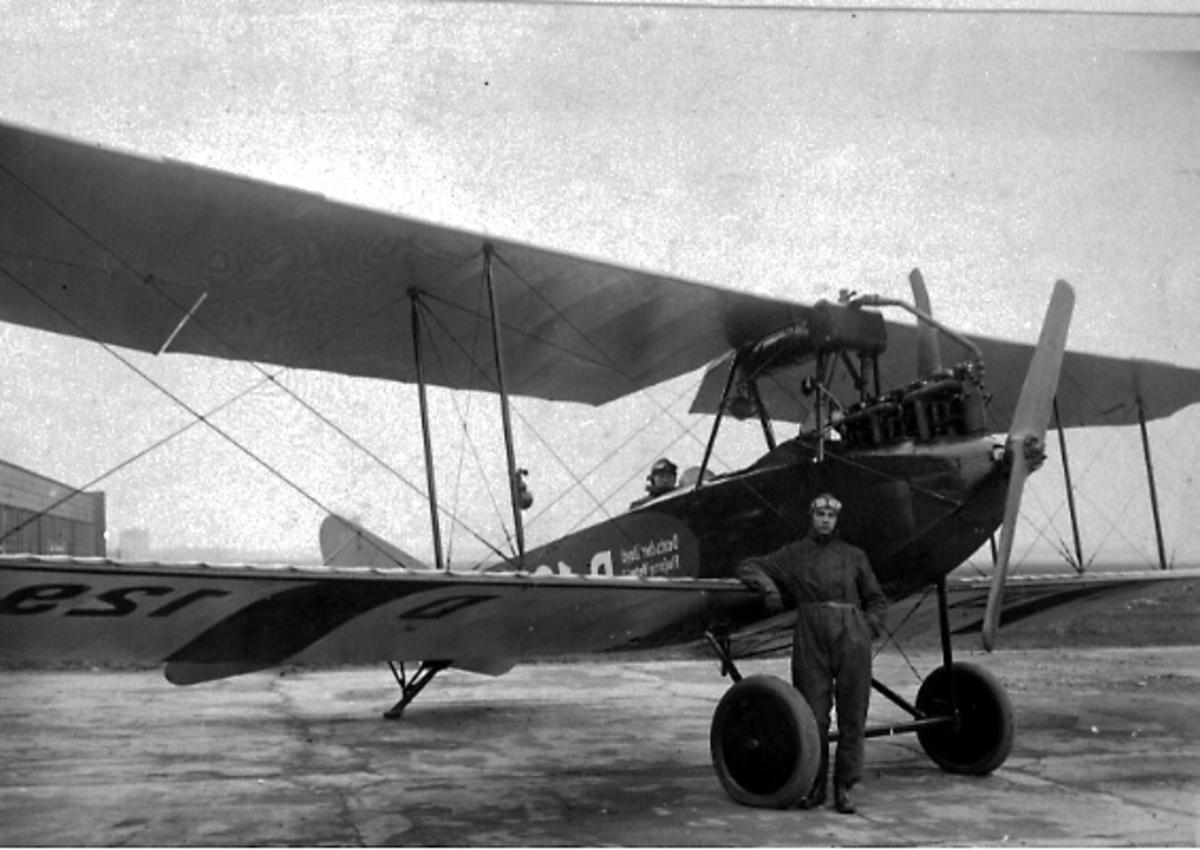 Ant. lufthavn. Fly på bakken, Albatros C.1. Skrått forfra. Person i cockpit, og en person står ved flyet, foran.