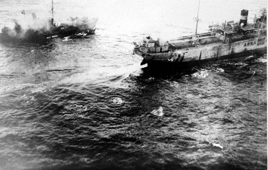 """Luftfoto,  2 fartøy nedenfor, foran ligger """"Arna"""". Røyk stiger til værs etter bombetreff. Hav rundt."""