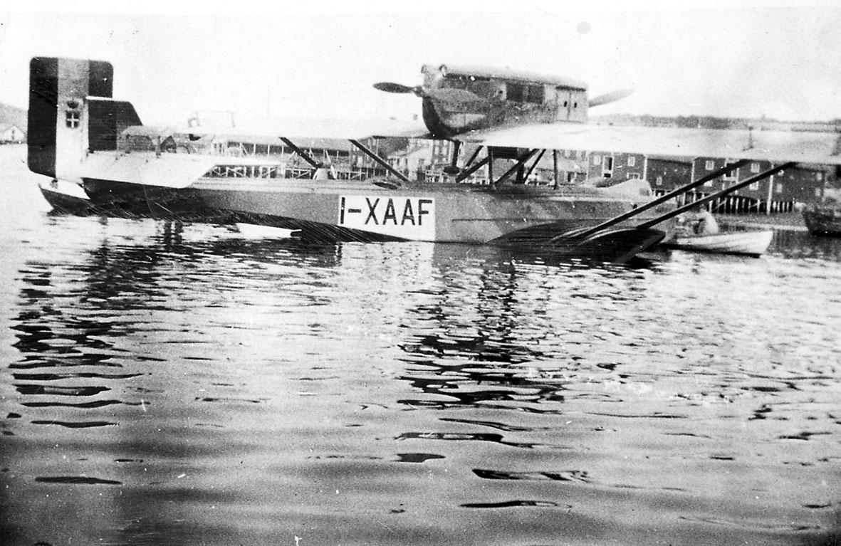 Havneområde. 1 fly på havoverflata, Dornier-Wal I-XAAF, skrått bakfra. Åpen robåt, med en person ombord, ligger ved flyet. Bak sees flere brygger på pæler.