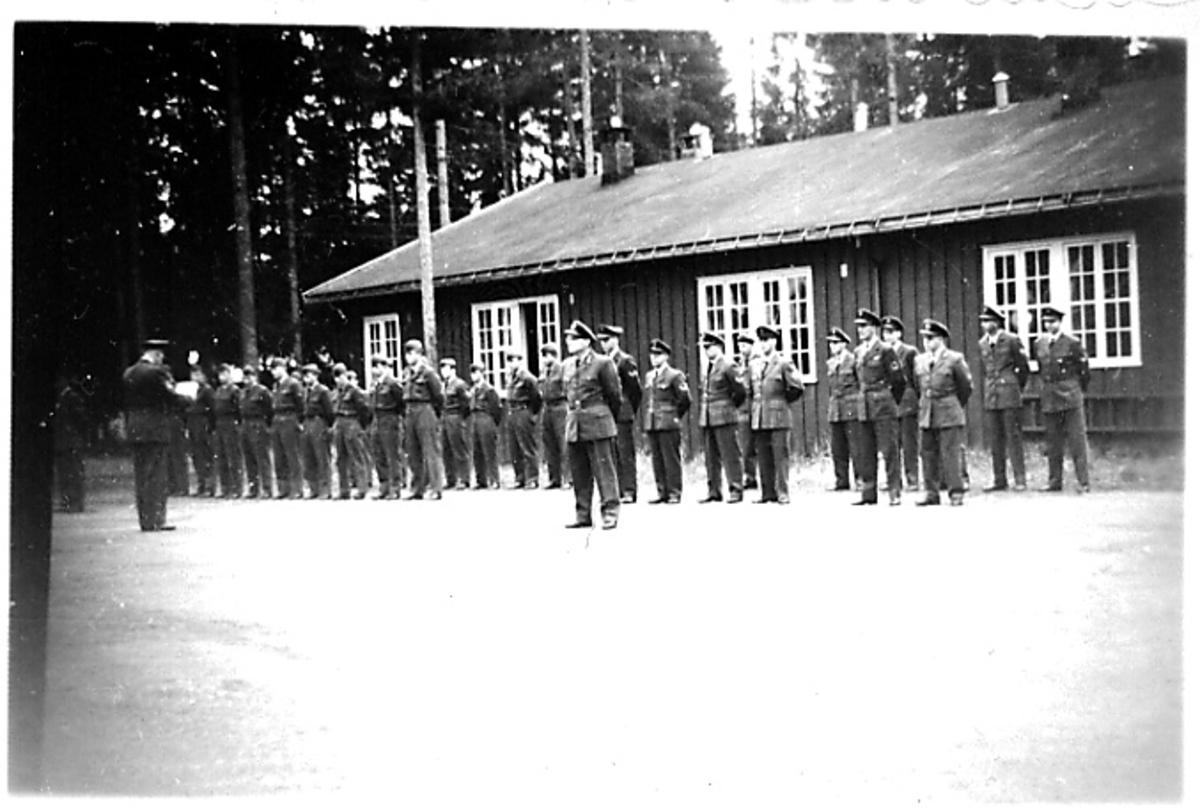 Mange personer oppstilt foran bygning. Militære, i militæruniform.