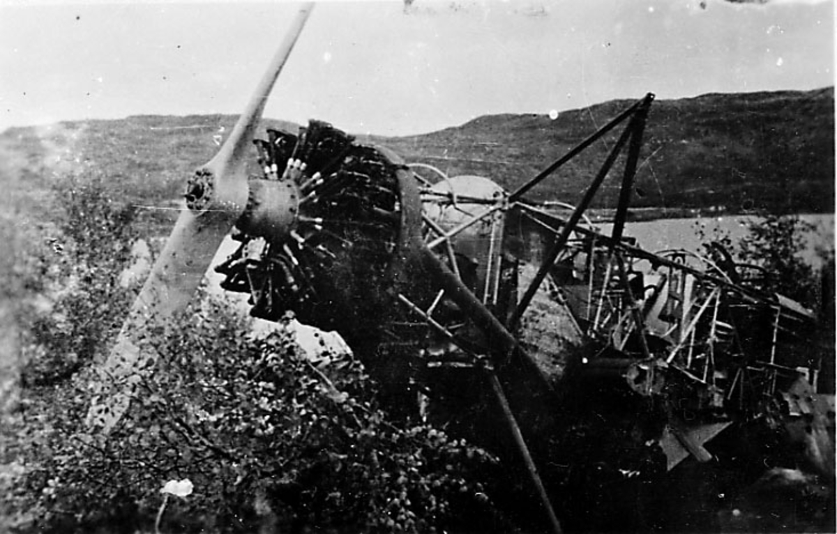 1 fly på bakken, flyvrak - ødelagt fly, norsk Fokker 381, nesepartiet skrått forfra mellom noe kratt.
