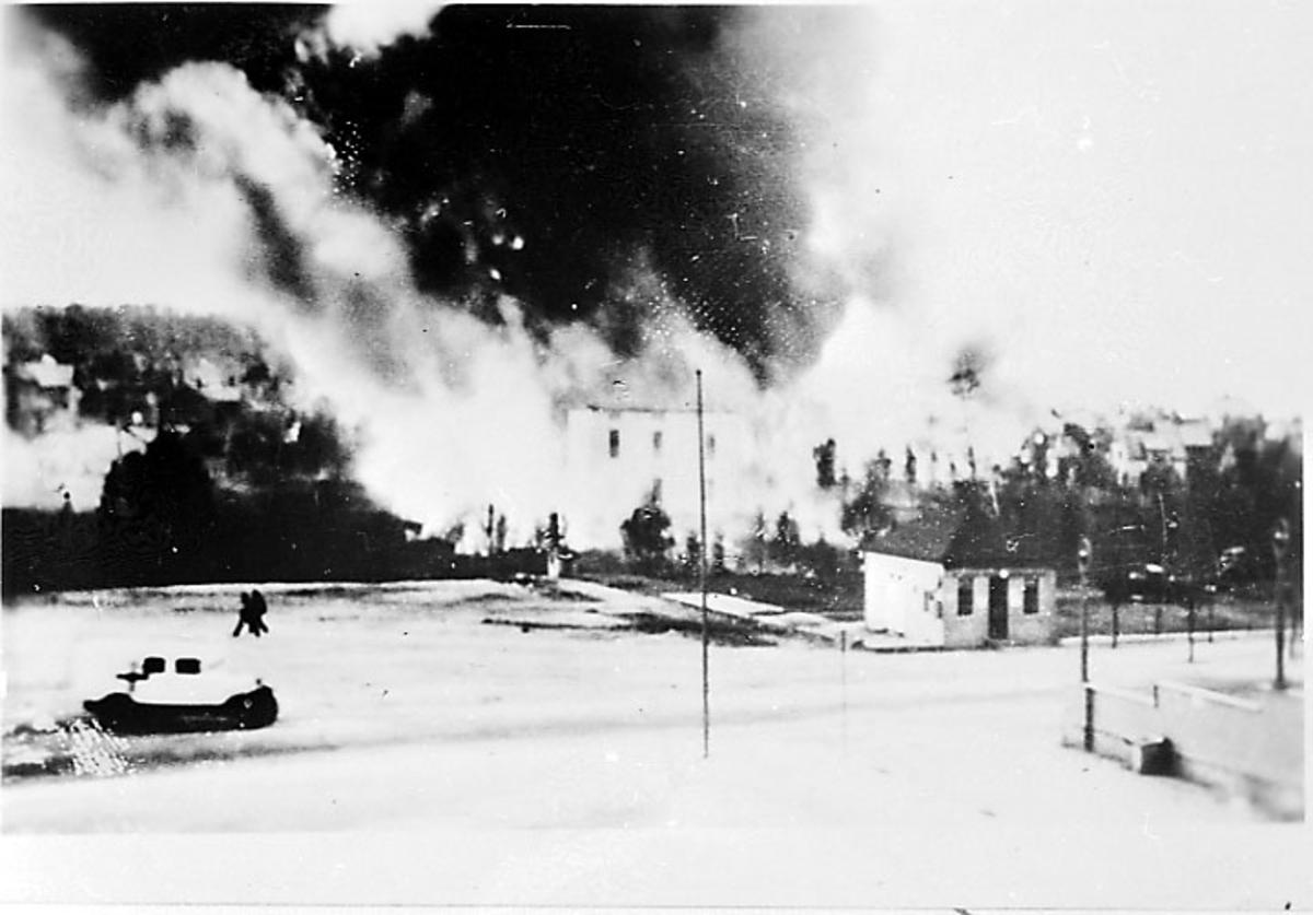 Røyk fra bygninger, i forgrunnen åpen plas med 2 personer. Narvik etter bombing - kriksødeleggelser, under 2. verdenskrig.