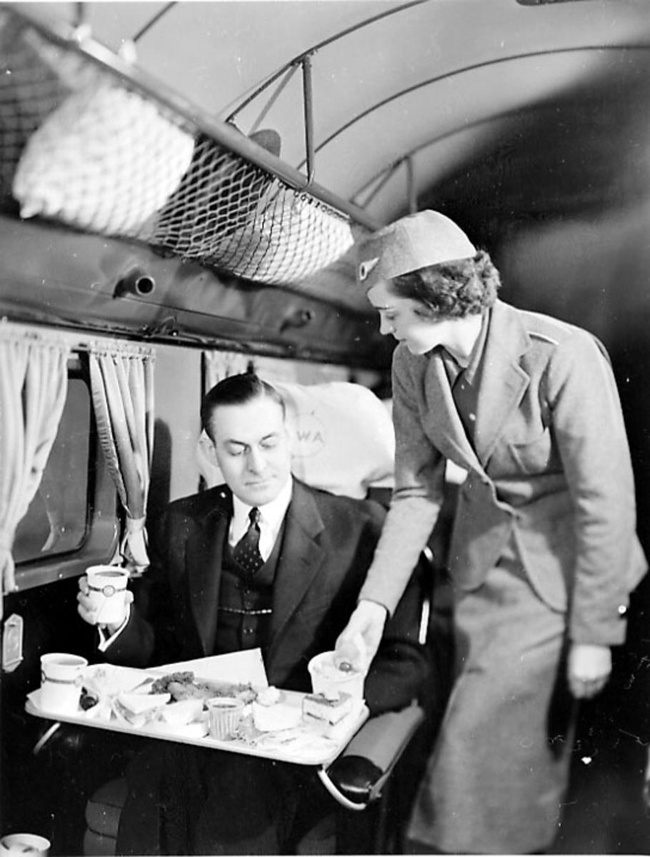 Inne i flycabinen på en DC-2. 2 personer. Flyvertinnen serverer mat til en passasjer.