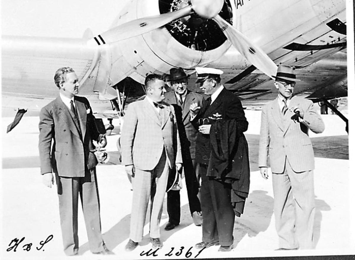 Lufthavn, portrett, 4 personer tatt utendørs, en av dem i flyuniformø. Litt av fly sees bak.