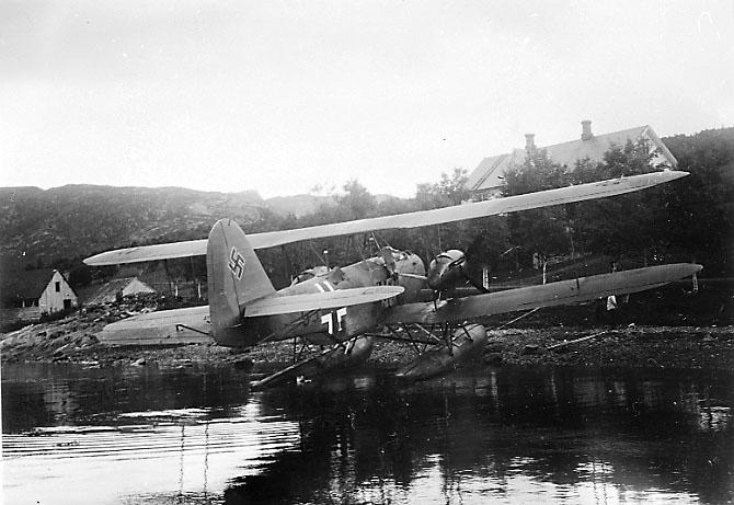 1 fly ved strandkanten, delvis oppe på land, Heinkel He 59 6J+ZK fra ZG.76. Sett skrått bakfra, hakekors på halepartiet.