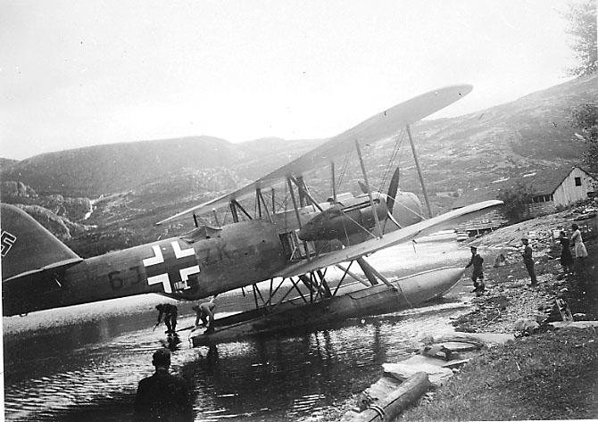 1 fly ved strandkanten, delvis oppe på land, Heinkel He 59 6J+ZK fra ZG.76. Sett skrått fra siden, hakekors på halepartiet. Flere personer på stranda og ved flyet.