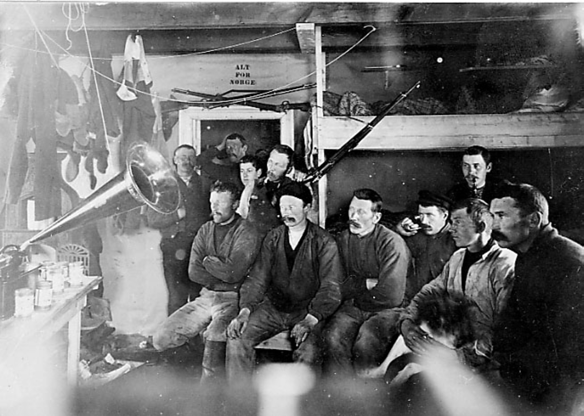 Walter Wellman Nordpolekspedisjon. Portrett av ekspedisjonsmedlemmer - arbeidslag, tatt innendørs. Perssonene sitter og hører på en gramafon e.l.