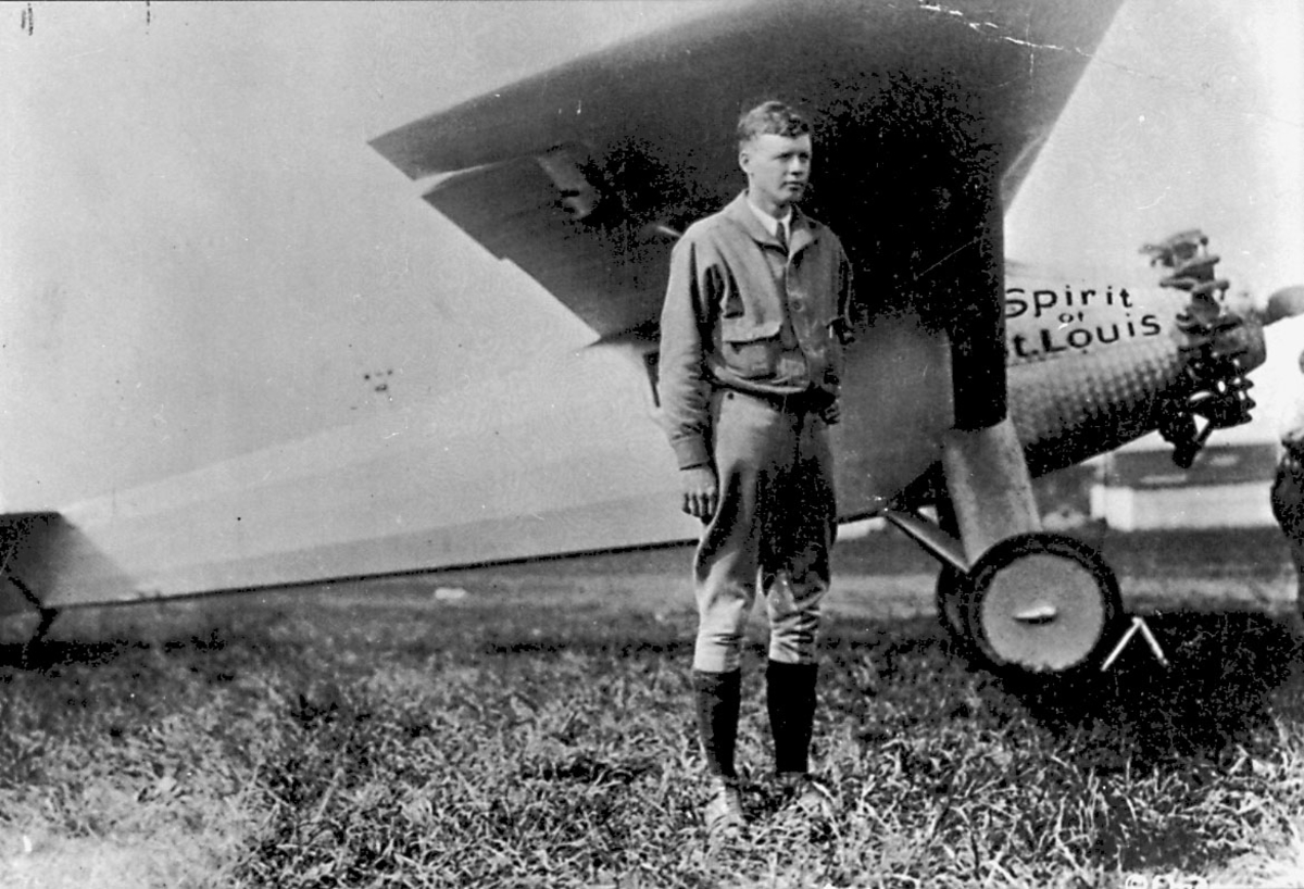 "Lufthavn (ant.) Portrett, 1 person, Charles Lindbergh, foran 1 fly, ""Spirit of St. Louis""."