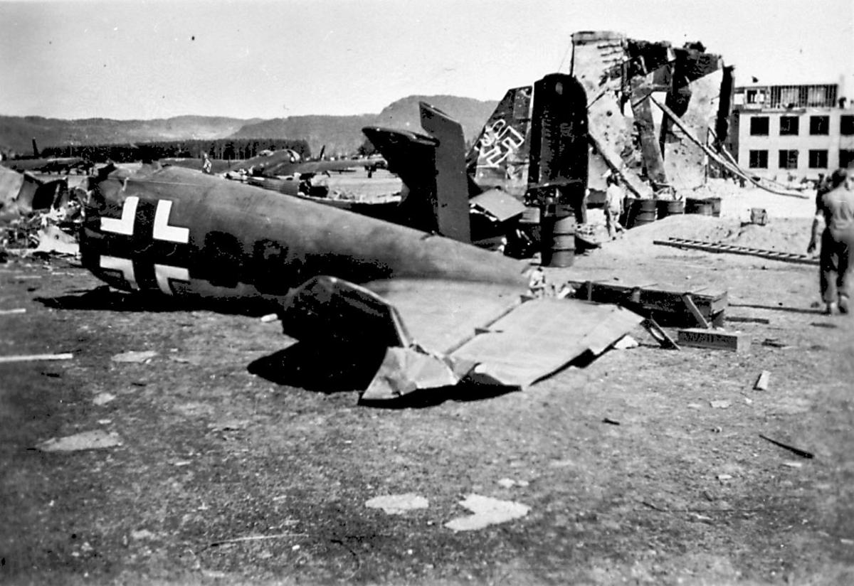 Vrakrester av 1 fly på bakken, Heinkel HE111 fra 8/KG261H+CS.  Andre vrakrester og fly i bakgrunnen.