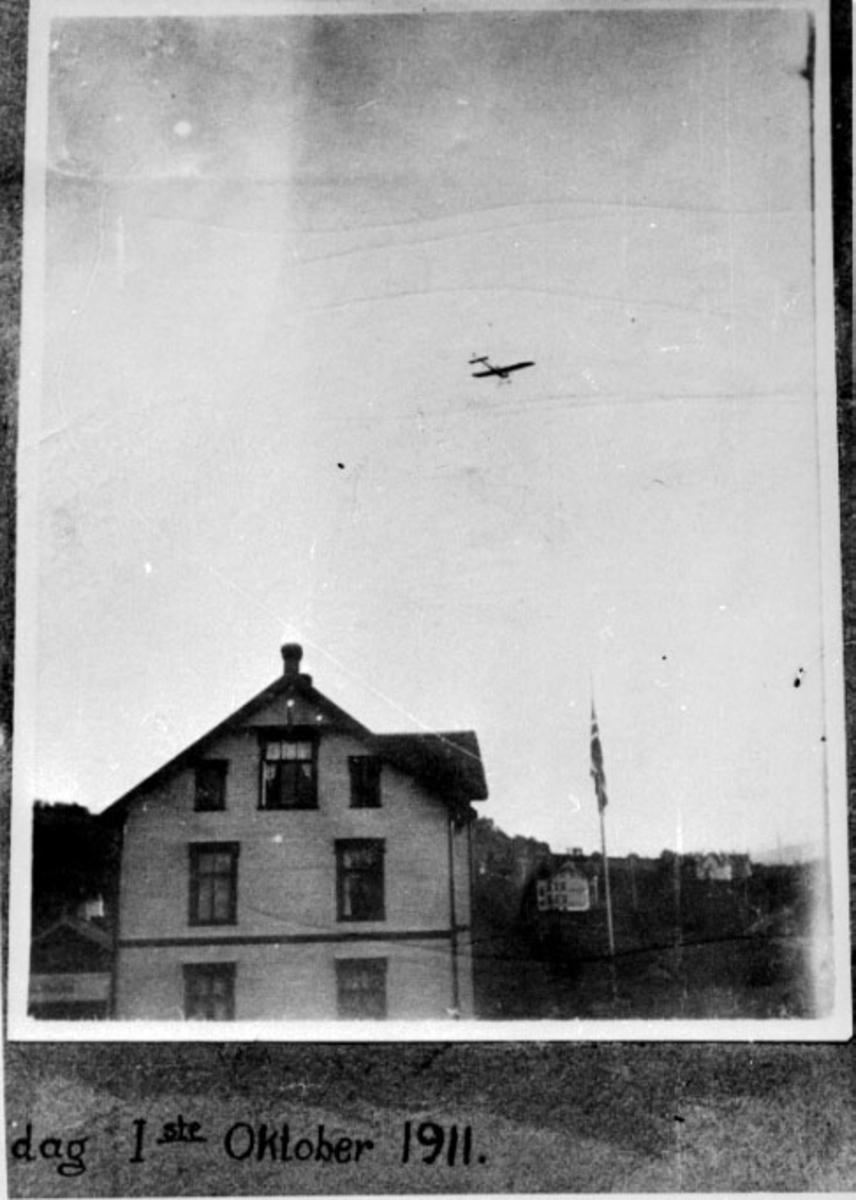 Bygning i forgrunnen. 1 fly i lufta i bakgrunnen.