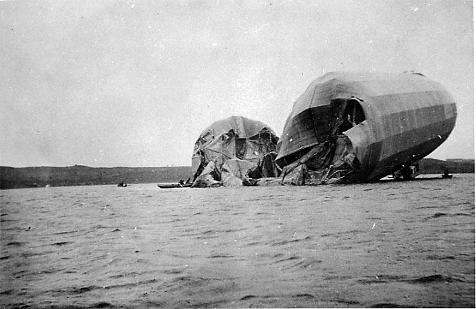 Havari - 1 lluftskip ligger ødelagt på havoverflata. Robåter med personer ombord ved luftskipet. Landskap i bakgrunnen.