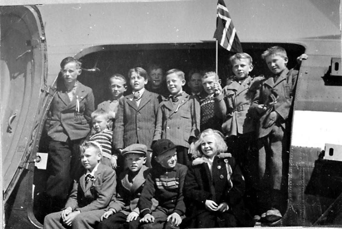 Gruppefoto, flere personer - unger - ved inngangsdøra til 1 fly. 1 av dem med det norske flagg i hendene. Tatt utendørs