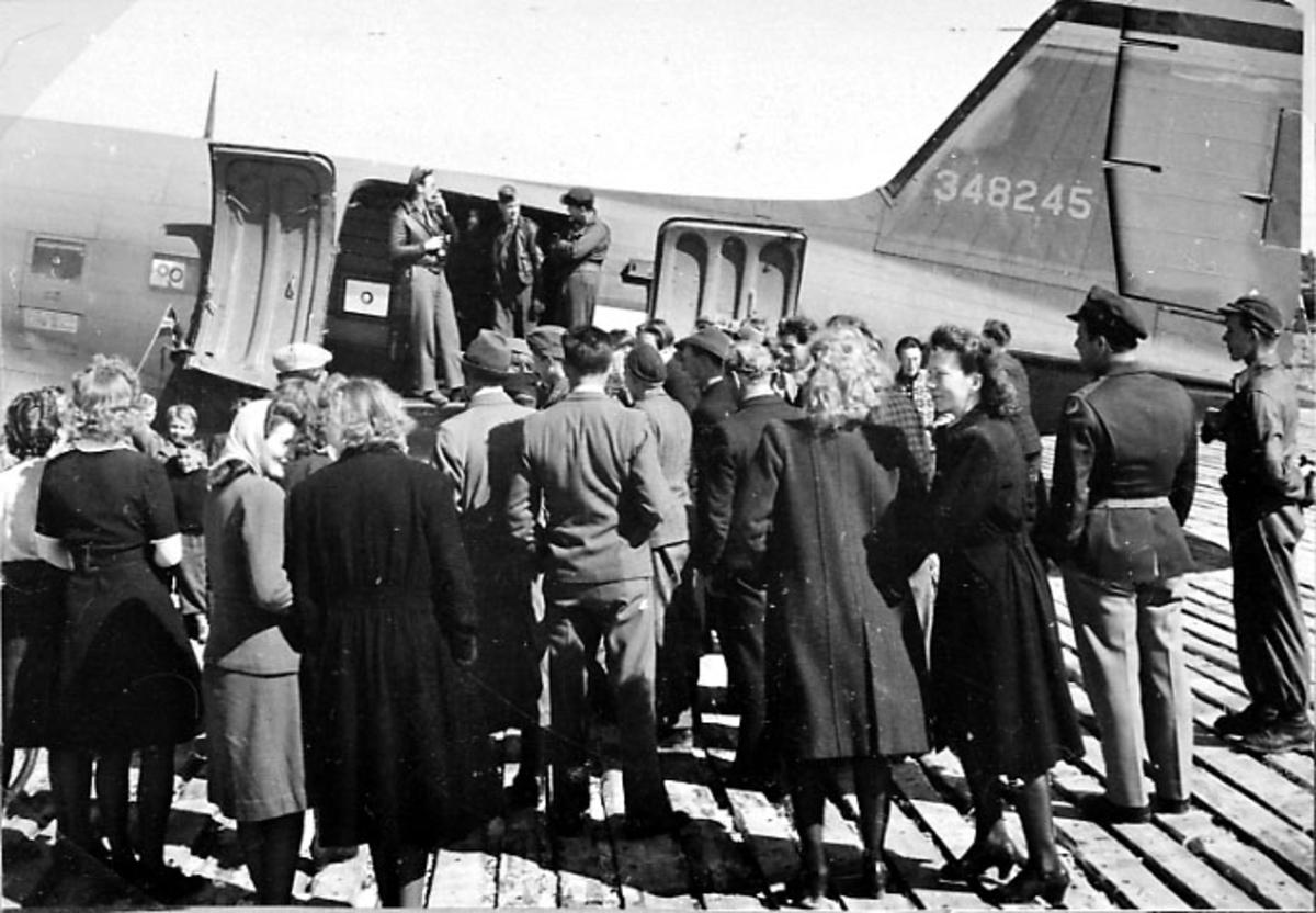 Flere personer står foran halepartiet på et fly, flyet merket 348245.