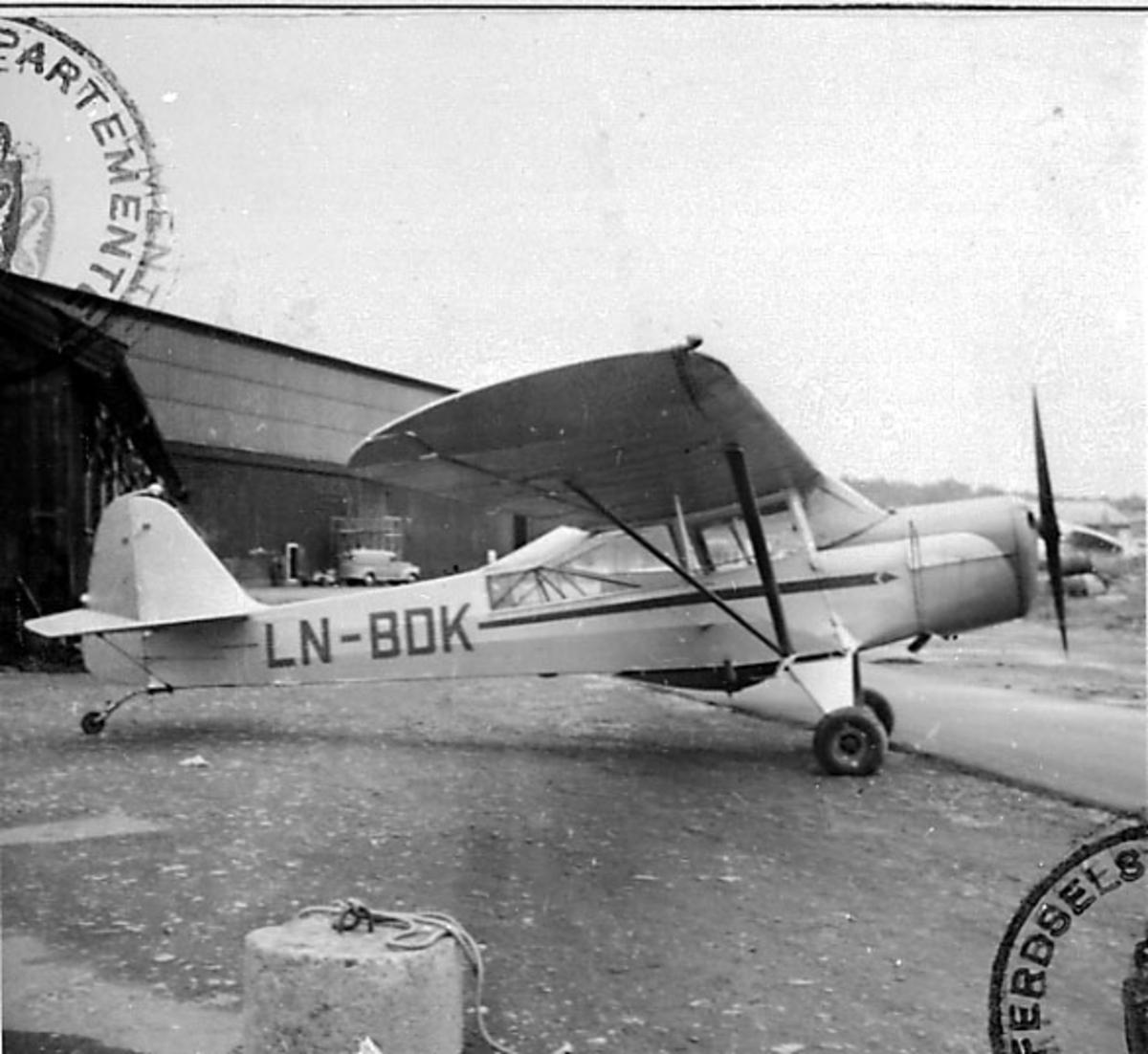 1 fly på bakken, Auster V LN-BDK fra Telemark Flyselskap A/S. Bygning bak.