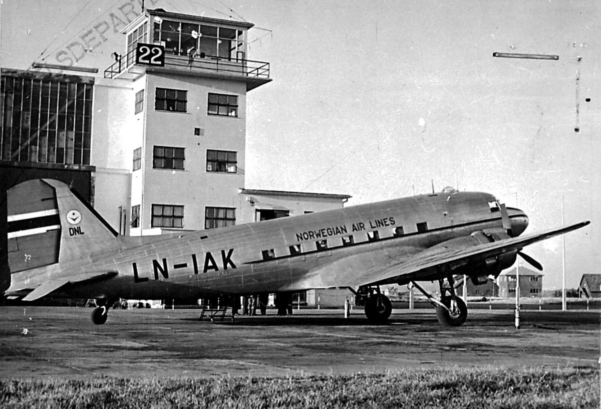 "Lufthavn, 1 fly på bakken, Douglas DC-3A C-53D, LN-AIK ""Knut Viking/ Nordkyn"" fra DNL A/S Oslo. Kontrolltårnbygningen i bakgrunnen."