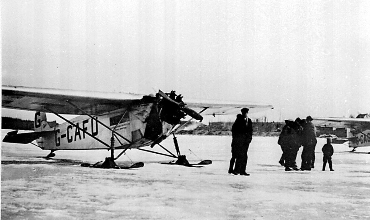 Flere personer ved 1 fly, Fokker Universal, G-CAFU fra Western Canada Airways. 1 annet fly i bakgrunnen. Bildet tatt ved Hudson Bay airlift i 1927.