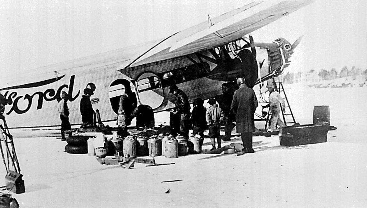 1 fly på bakken, Ford. Flere personer og en del utstyr ved flyet. Ant. ekspedisjonsforberedelser.