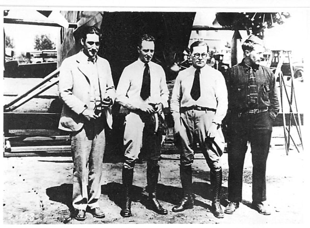 """Portrett, 4 personer foran 1 fly, Fokker C-2 C-2A """"America"""". Bruker: Admiral Byrd. Tatt utendørs."""