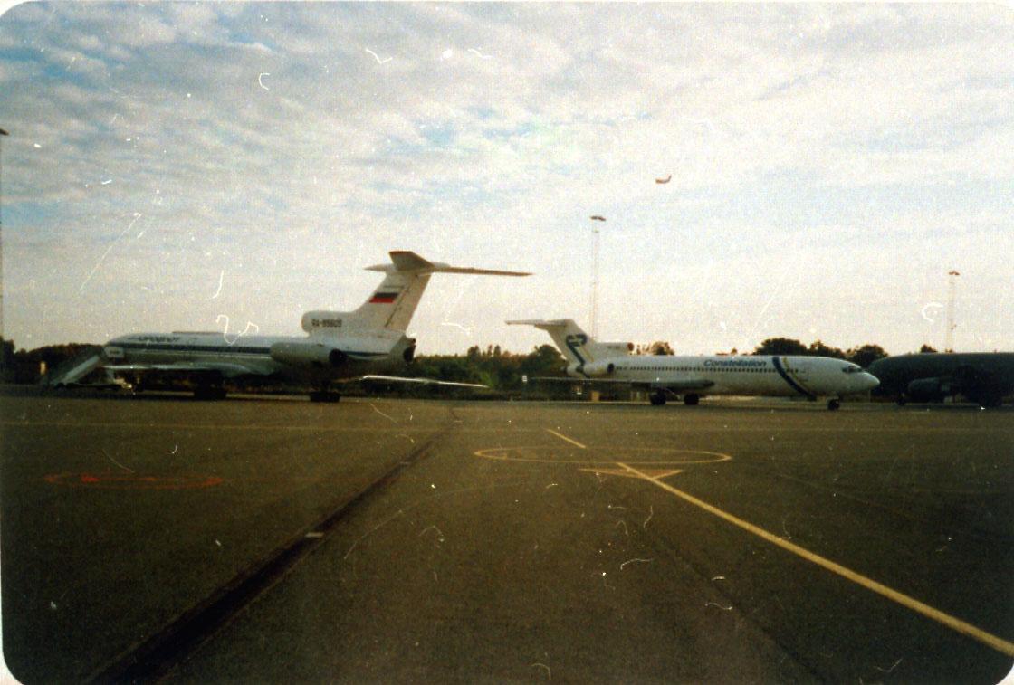 Lufthavn, 2 fly på bakken, foran Tupolev 154, RA-B5605. Bak Boeing 727. Litt av rullebanen i forgrunnen.