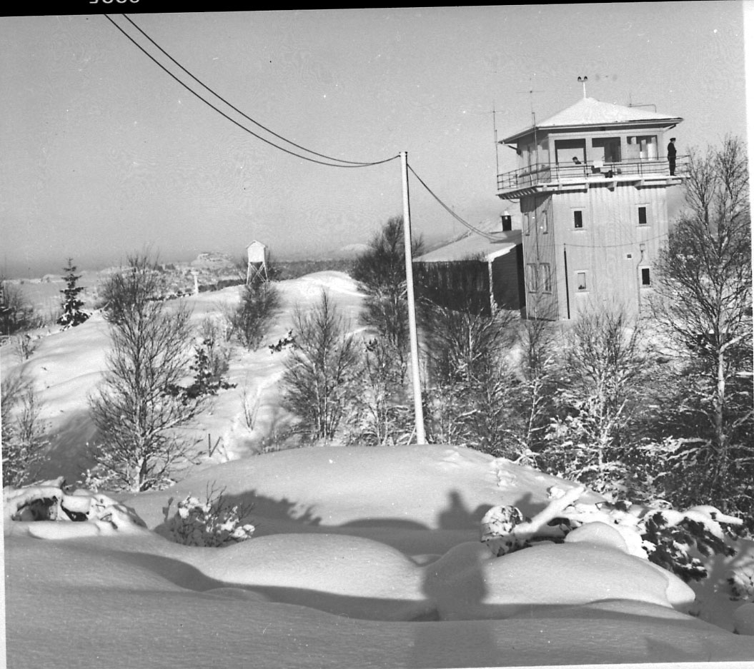 Lufthavn, kontrolltårnet i forgrunnen. Snø på bakken.