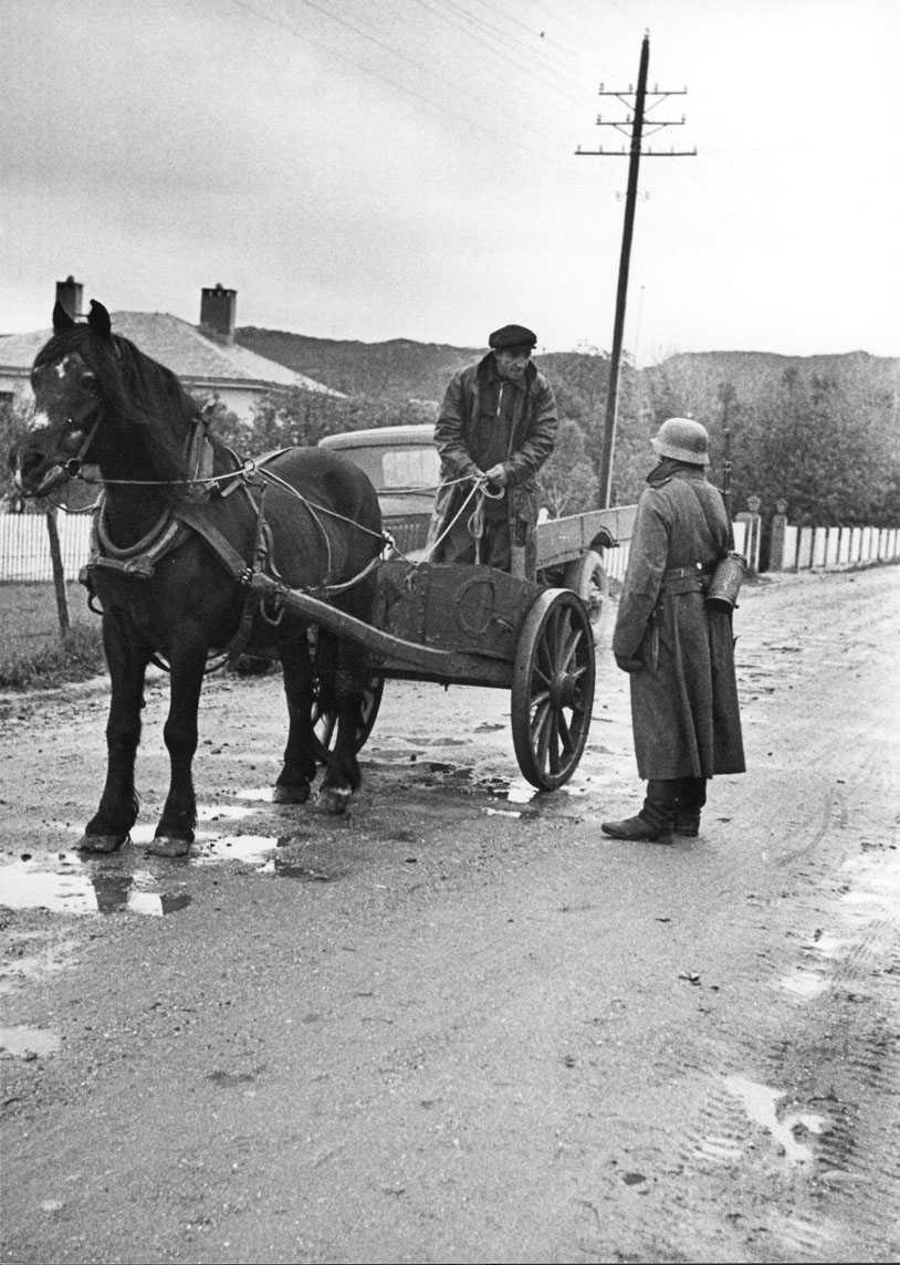 "Hest og kjerre - vogn. 1 person står i vogna og ""snakker med 1 person i militæruniform Tysk soldat. Sansynligvis på snippen."