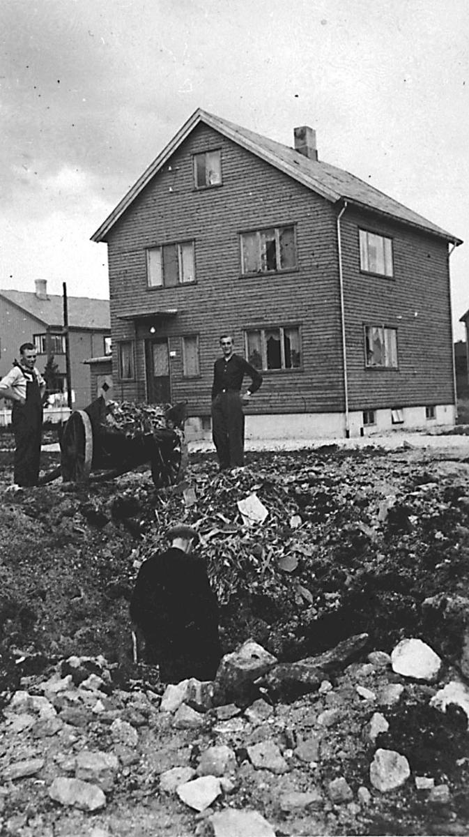 Tettsted/by. Bombenedslag/krater i bakken. Noen personer. Bygning, Wiks hus, bak.