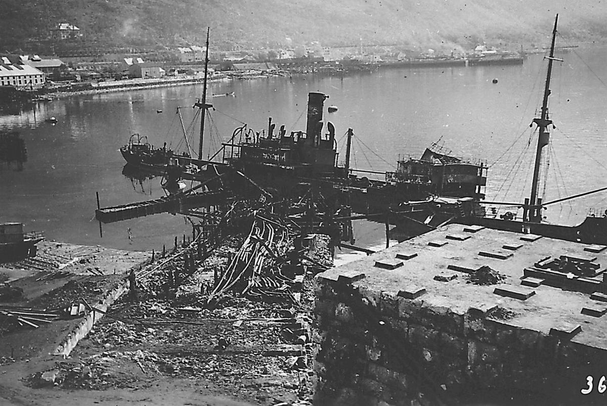 Tettsted/by. Havneområde med 2 fartøy. Havneområdet og fartøyene ødelagt etter bombeangrep. Bygninger i bakgrunnen.