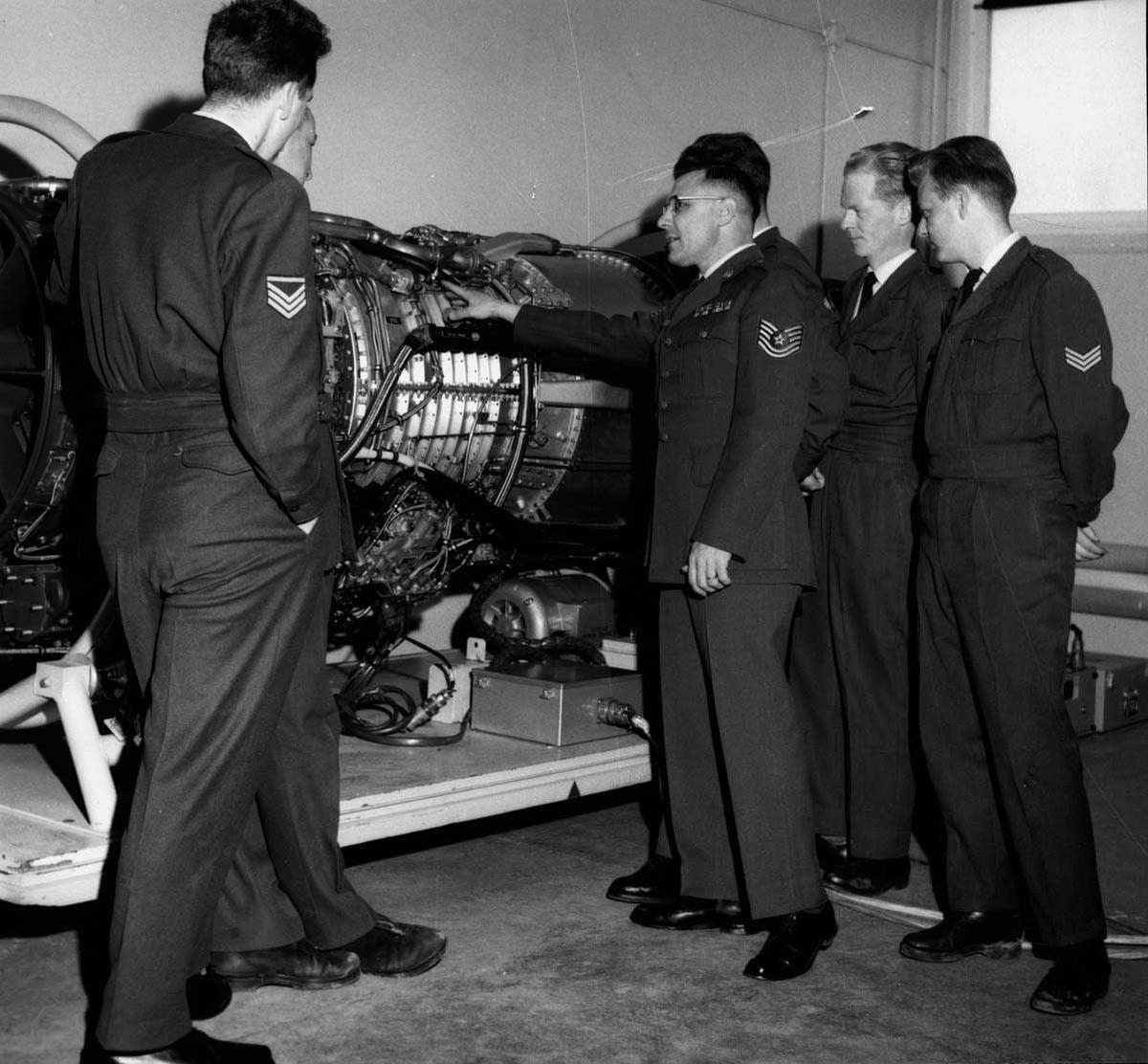 Gruppe.  Seks personer i uniform ved siden av en jetmotor.