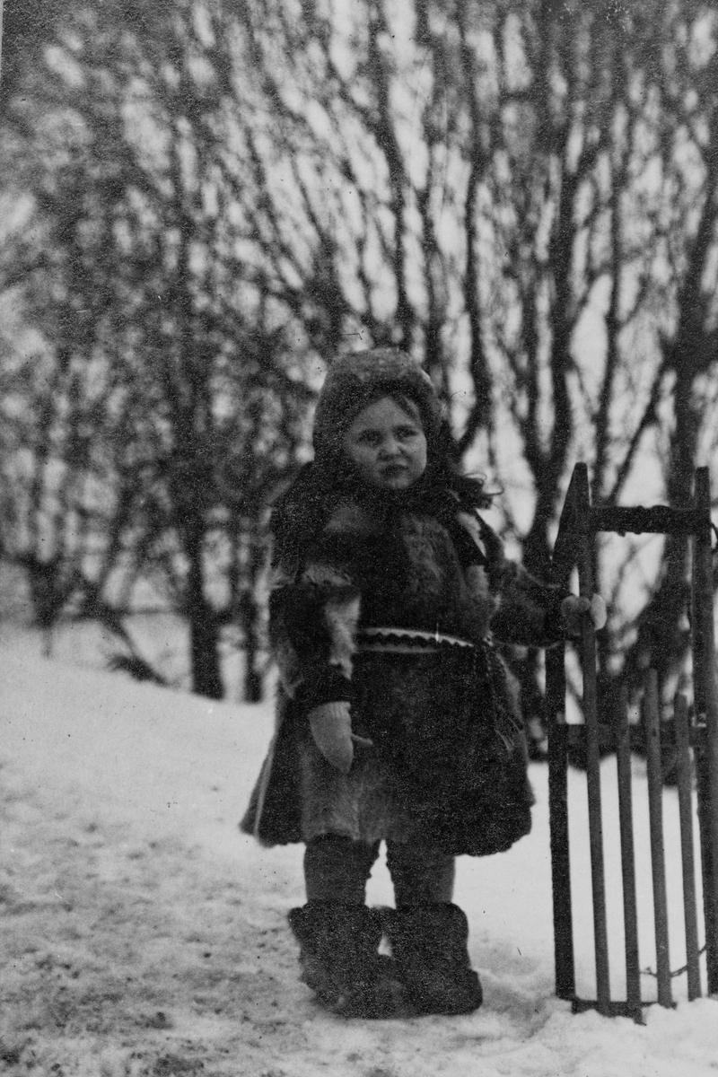 Lita jente i pelsklær står med en kjelke, fotografert i snøen utendørs.