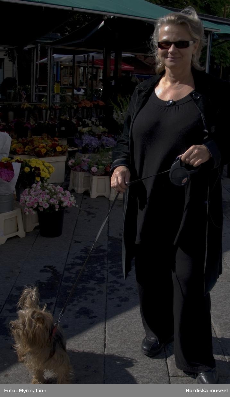 Foton tagna av elever från Mediagymnasiet i Nacka. Eleverna fick i uppdrag att  till Nordiska museets webbplats om kläder och mode leverera bilder från vardagen i Stockholm i september 2010. Glad kvinna på promenad med sin hund, Östermalm. Solglasögon, svarta kläder.