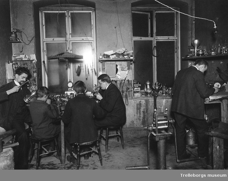 Martin Lysells guldsmedsverkstad, Östergatan 3, Trelleborg. Längst till vänster sitter Martin Lysell själv, sedan följer Anders Malmberg, Gustaf Olsson, Teodor Balte och Lars Wirgin. Verkstaden startades 1904 av Martin Lysell.