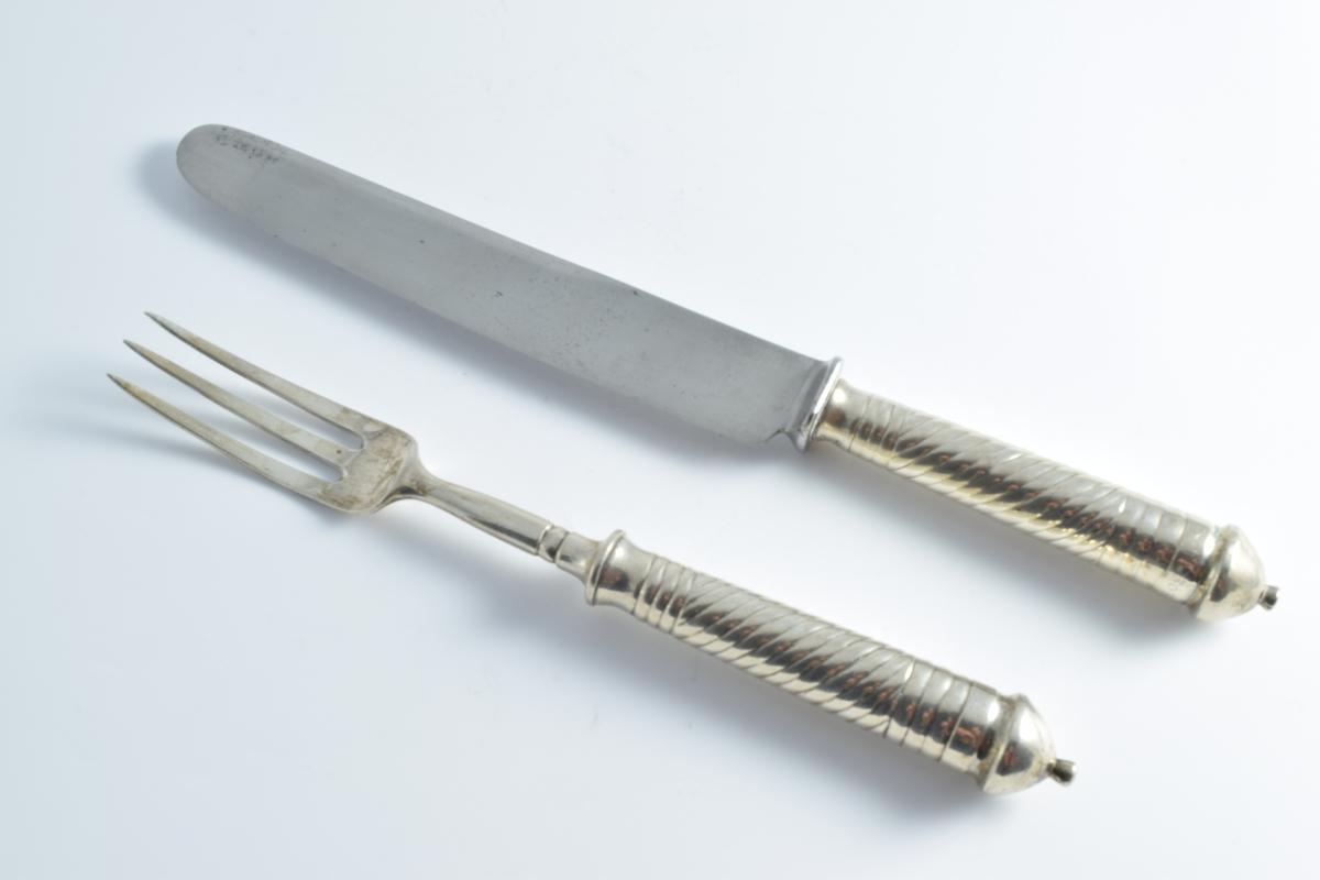 Et sett med kniv og gaffel i sølv. Skaftene er kraftige og er dekorert med spiralformede linjer,.