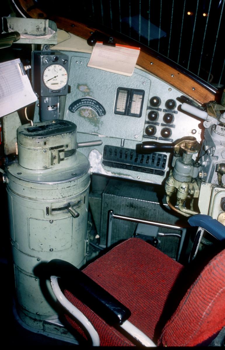 Førerplass i NSB dieselelektrisk lokomotiv Di 3 603, førerrom 2. Di 3 var lisensprodusert hos Nydquist och Holm Aktiebolag i Sverige med utstyr fra GM-Electro Motive Division. Det meste utstyret her er originalt GM-EMD utstyr. Fra venstre ser vi konsollen med kjørekontroller. Denne utgaven av konsollen hadde lokomotivene 602 - 606, mens senere lok fikk en mer moderne rett variant med bakelitt-håndtak. Over konsollen er registrerende hastighetsmåler (Hassler). Videre har vi panelet med amperemeter for motorstrøm, manometre for bremsesylindertrykk, hovedledningstrykk og hovedluftbeholdertrykk. Til høyre på panelet er div varsellamper, og nedenfor brytere for forskjellige funksjoner i batteristrømskretsen (72V) som f.eks. signallamper, frontlys, førerromsbelysning, oljepumpe, mm. Helt til høyre er førerbremseventil Knorr St15 for direktevirkende brems og Knorr D2 for automatisk virkende brems (indirekte brems/togbrems).