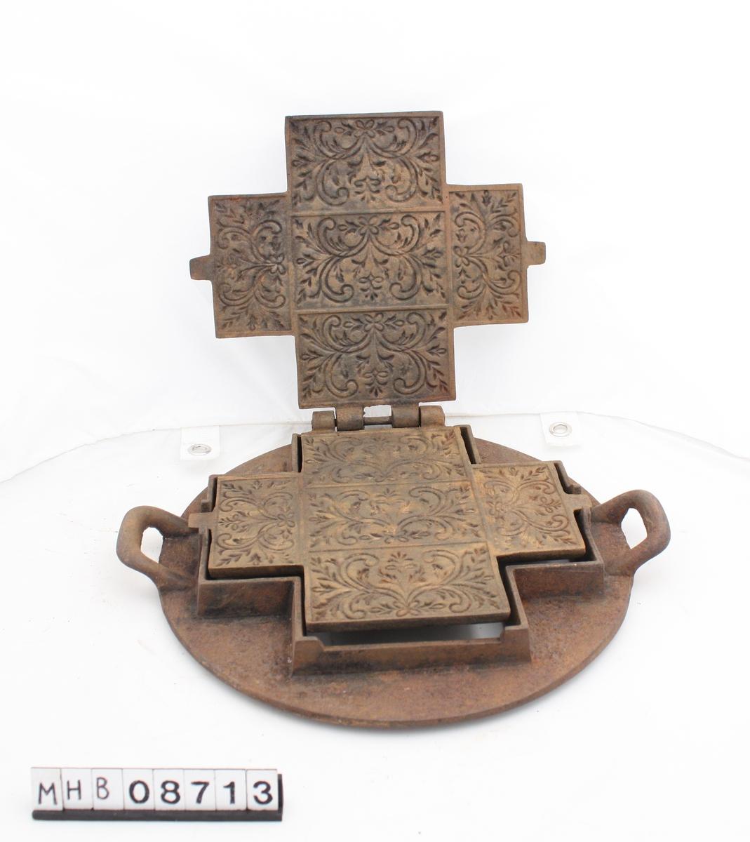 """Rundt stativ/ramme med håndtak på hver side. Selve kakejernet (stekeformen"""" """"firearmet"""" med 5 rektangelformede, mønsterfelt innvendig. Lokk og bunn hengslet sammen. Kan løftest av stativet/rammen. Bøylehåndtak på oppsiden av lokket.   På lokk inngravert: O.M. E.S. No. 4."""