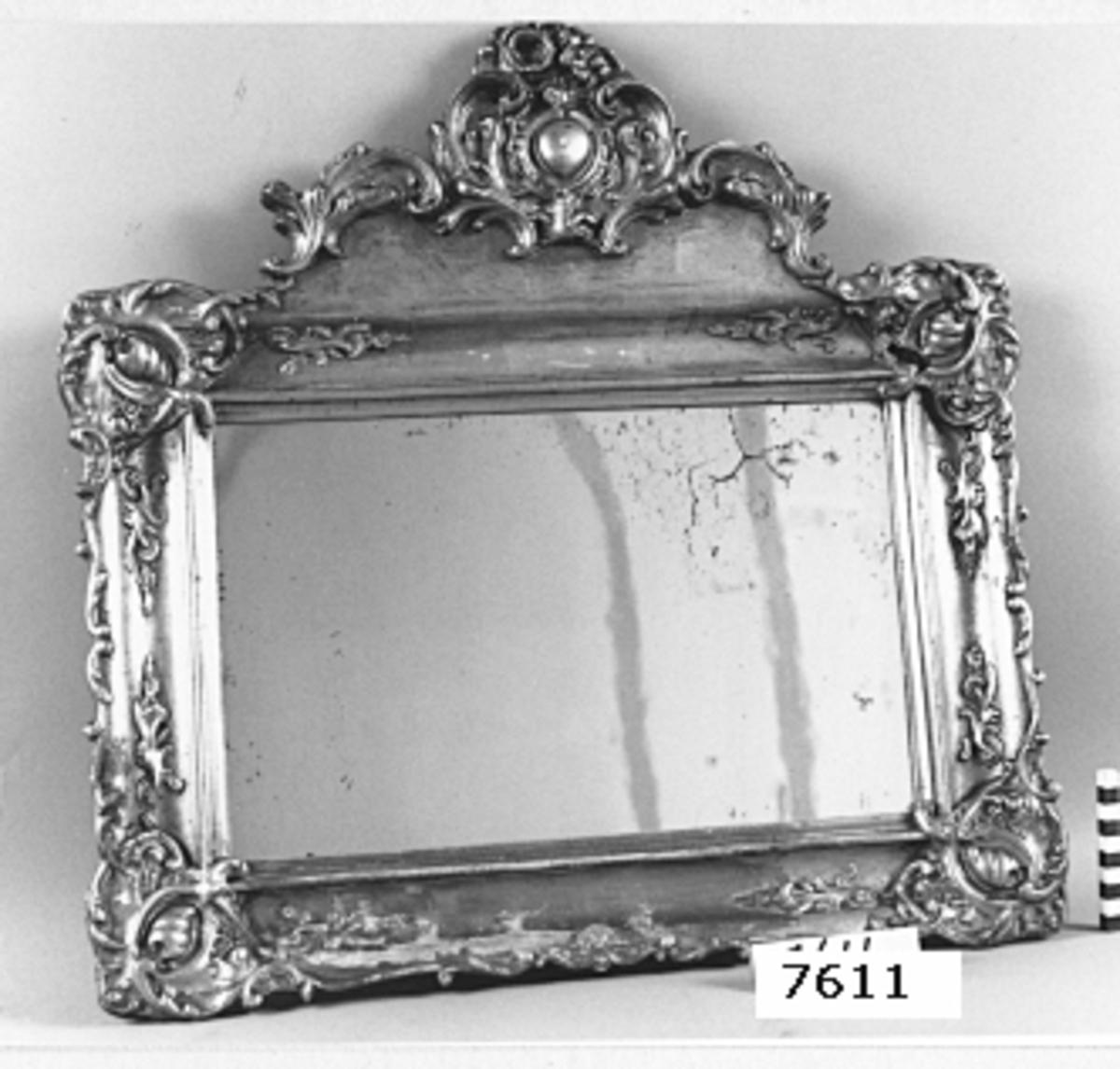 Spegel med förgylld ram av trä och gips. Ramen i barockstil med ornament i gips.