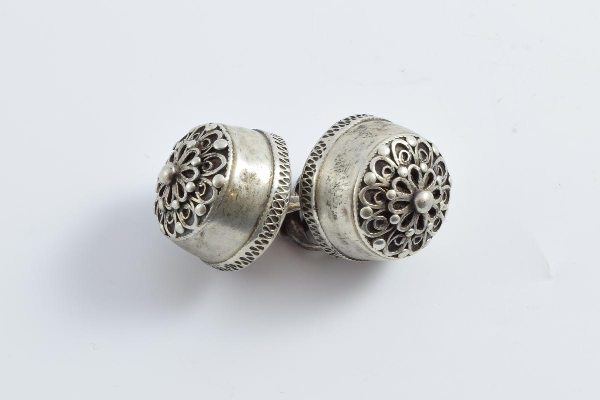 Halsknapper i sølv prydet med 8-bladet lokkerosett i en krans av 10 lokker. Mellom lokkene og i rosettens sentrum er det små perler.