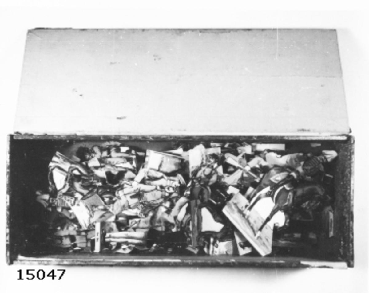 Pappfigurer, soldater i låda. Figurerna visar soldater i 1800-talstyp av olika utformning och i olika färger. Har pappersstöd på baksidan för att kunna stå upprätta. Antagligen tyskt ursprung. Till antalet ca 100. Lådan av typ cigarrlåda av märket Vertala.