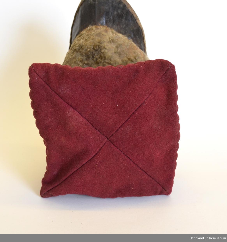 Pullen sydd av rødt ullklede (vadmel). Vattert. 8 cm bred kant rundt lua av saueskinn. Brem/skygge av garvet lær. Lua er fòret med grovt linlerret. Firkantet pull sydd sammen på toppen av 4 trekanter med spilesøm. 8-9 cm bredt vattert stykke fra skinnkanten og opp. Loddrette stikninger. Linfòret er rynket sammen inne i lua slik at det dannes et hull i midten.