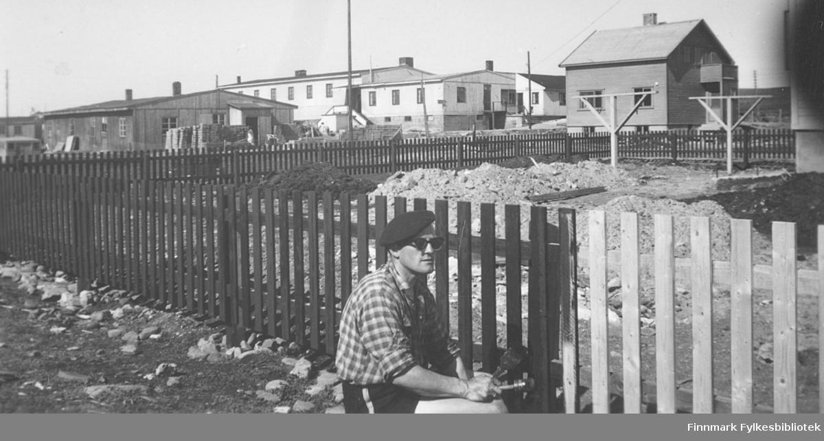 Fritz Ebeltoft maler det nye gjerdet rundt familiens hus i Fossevn. 3. Gjerdet ble satt opp i 1954. I bakgrunnen ser vi andre hus under bygging i området