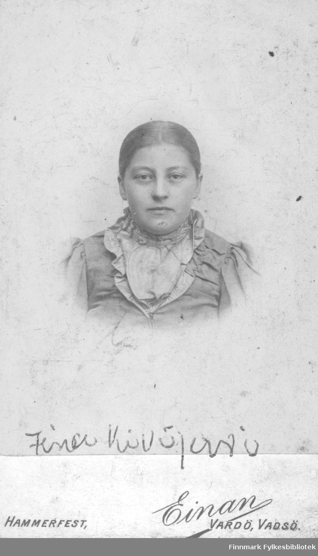 """Portrett av Fina (?) Kivijervi, tatt av fotograf Einan.   I Vadsø er det på denne tiden registrert en Brita Kaisa Kivijervi, født 1843 I Finland, innflyttet til Norge i 1872 og gift med Isak Kivijervi, fisker, født 1842 i Finland. Isak og Brita har en datter Ida Jesefina Kvijervi, født 1878. Det er muligens Ida Jesefina, forkortet til """"Fina"""", som er avbildet her. Ida Jesefina Kivjervi, født 1878 i Vadsø er registrert i folketelling i 1885."""
