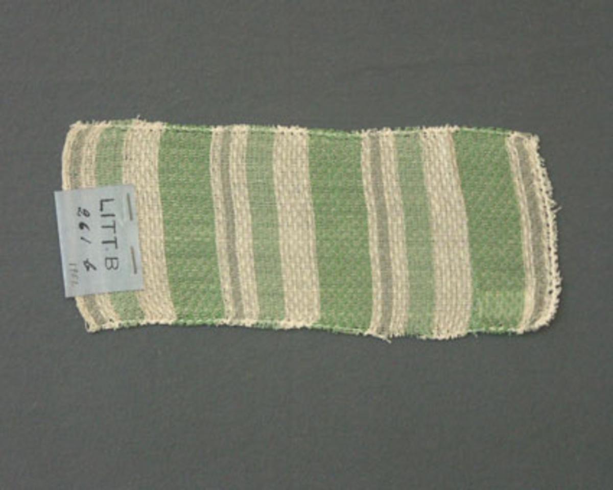Prov till gardin vävd i korndräll. Provet har bomullsgarn i varp och inslag.Ytterligare prov och vissa vävuppgifter finns i pärm gardiner A, litt B 261 b.