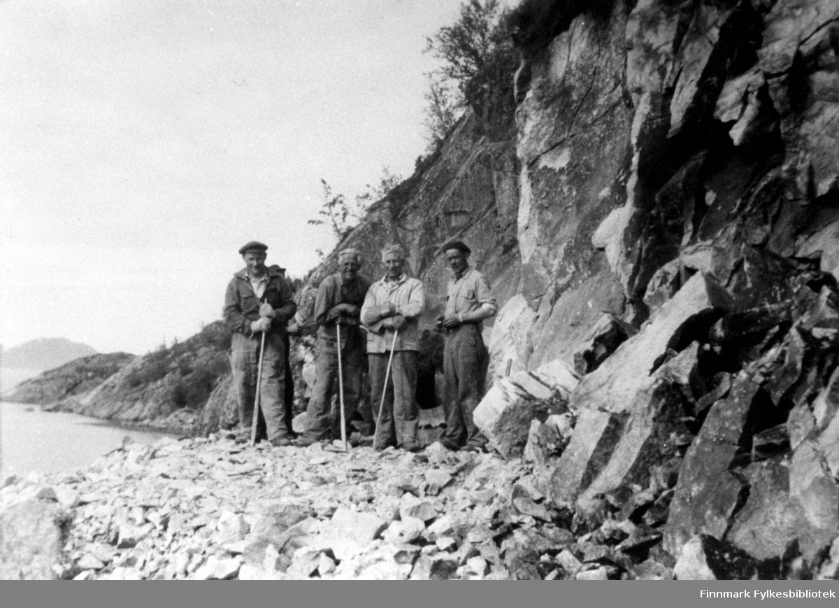 Portrettfotografi av fire menn som står ved et lite fjell. De holder på med fjellakkord. Fra venstre: Oskar Hansen, Håkon Rapp, Peder Israelsen og Iver Johansen.
