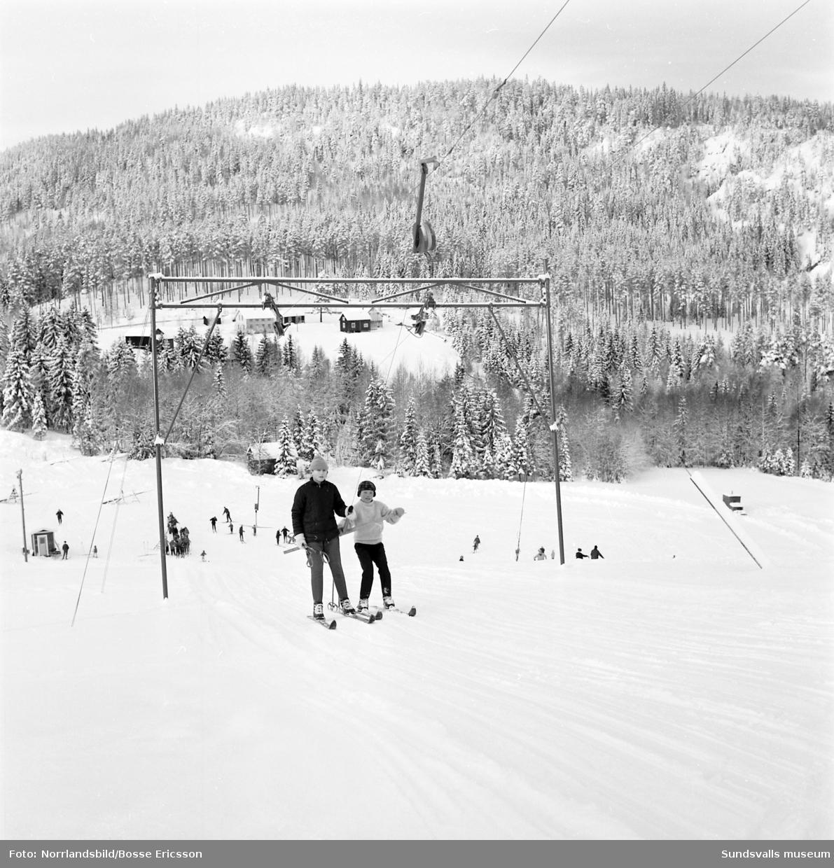 Bilder från skidbacken på Vättaberget, Liden. Vuxna och barn på väg upp i liften samt utsiktsbild från toppen av backen.