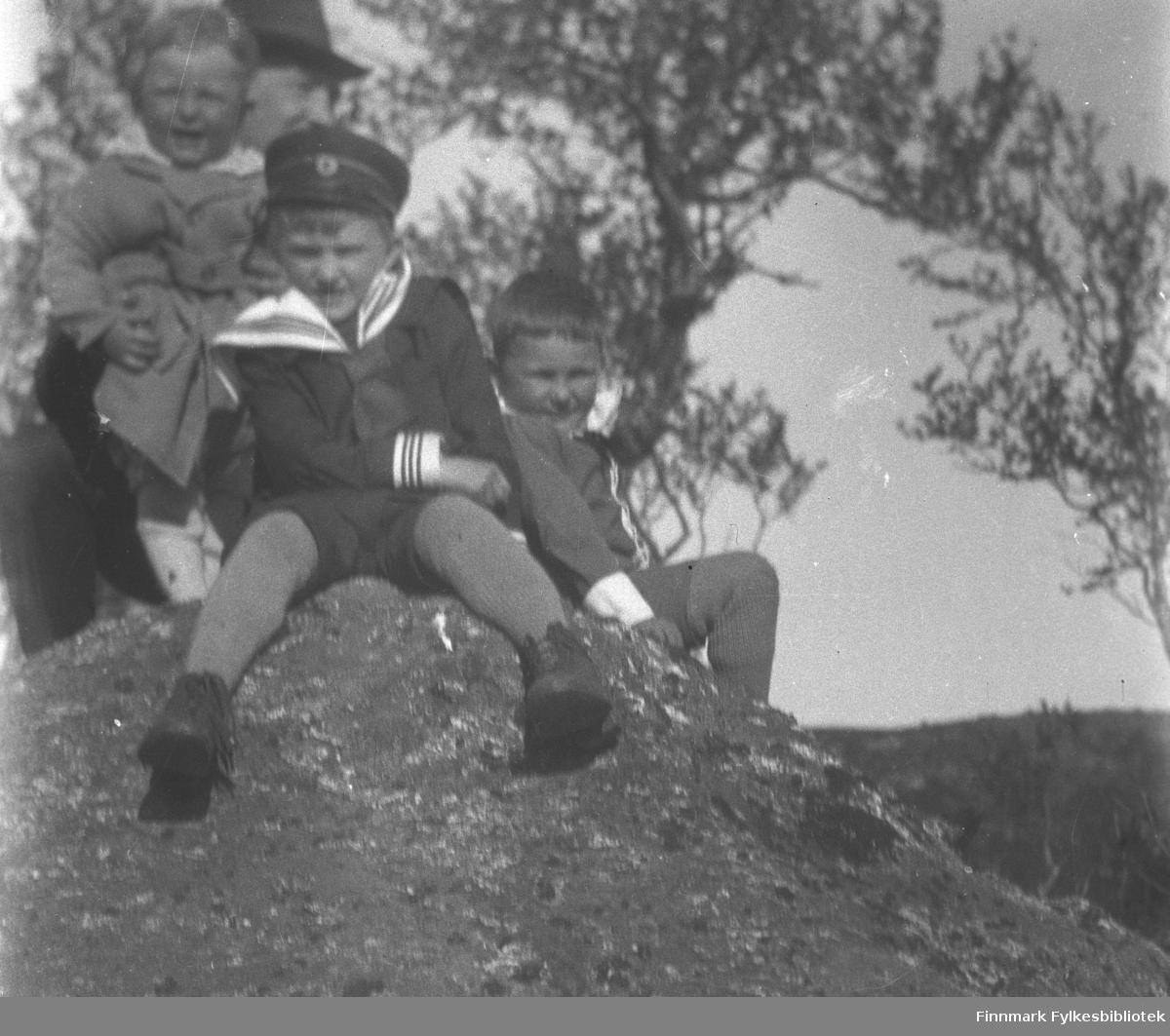 Portrett av fire personer på en stor stein. Gutten i matrosdress og lue, i midten på bildet er Fridtjof Johan Jacobsen. Til høyre for ham sitter Alf E. Jacobsen og bak til venstre står Ragnvald Jacobsen som blir holdt oppe av Frithjof Jacobsen. Alle guttene er sønnene til Frithjof Jacobsen. Et stort tre ses noe diffust i bakgrunnen.