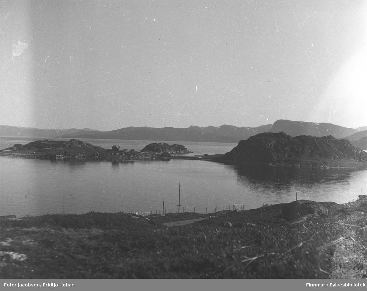 Klokkerøya, til høyre på bildet, utenfor Hammerfest/Rypefjord en sommerdag. Ved siden av Klokkerøya er Strømsnes. Bebyggelse ses langs strandkanten på halvøya. Terrenget foran på bildet er stort sett gress- og lyngdekt og Akkarfjorden har blikkstille sjø. En del stolper, både gjerdestolper og el-stolper står på området. Fjellene i bakgrunnen er Seiland. Sannsynligvis er bildet tatt før andre verdenskrig