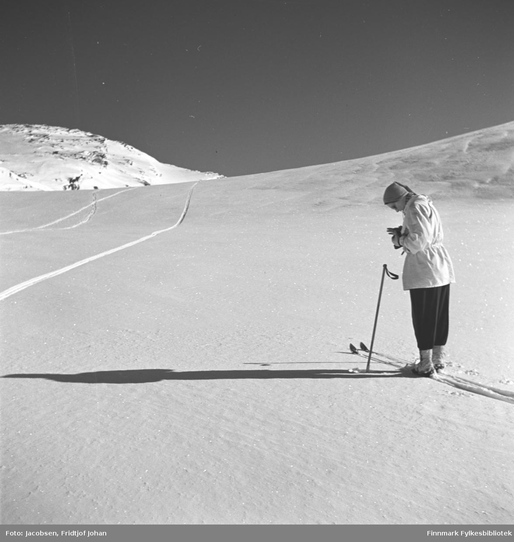 Aase Jacobsen på skitur. Hun har en mørk bukse og lys anorakk på seg. Hun er også iført lyse ullstrømper og lue. Hun holder noe i hendene, muligens et fotografiapparat. Det ganske flate og snødekte terrenget er rett ovenfor Jansvannet. En fjelltopp ses oppe til venstre på bildet.