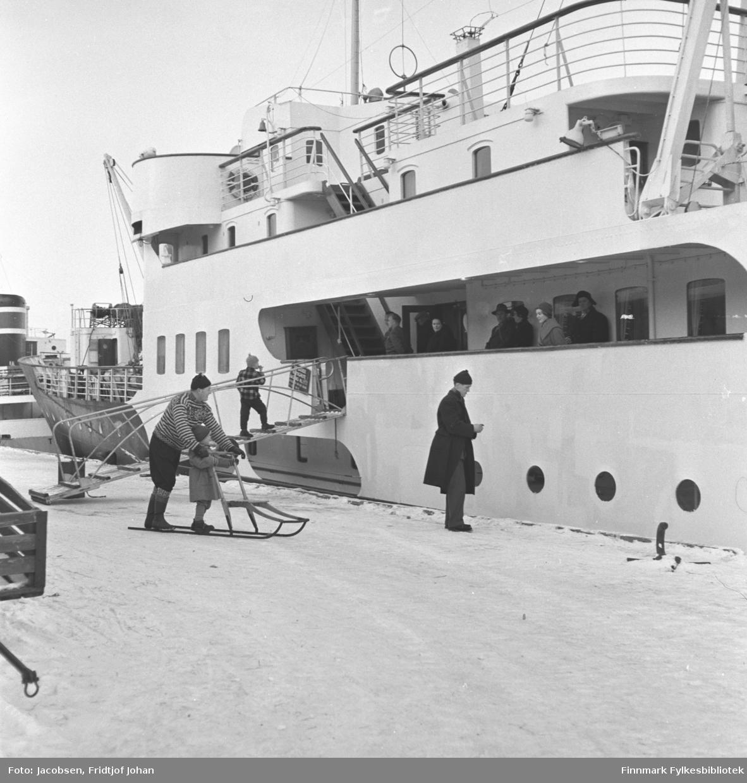 Hurtigruten Ragnvald Jarl klar for avgang fra Hammerfest havn. Flere personer står på dekk og en gutt er på tur opp landgangen. En mørkkledt person står på kaikanten og en mann med spark er like bak. En jente står på meiene til sparken. En liten del av et overbygg og en skorstein til en annen båt ses til venstre på bildet.