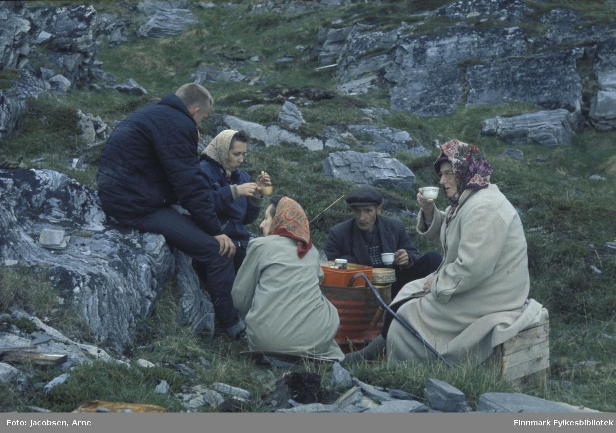 Et pust i bakken. De er, fra venstre: Arne Jacobsen med mørk bukse og boblejakke. Foran han sitter Aase Jacobsen med mørk jakke og lyst tørkle på hodet. Sigrid Nakken, men ryggen til, har lyst kåpe og mønstret tørkle på hodet. Arne Nakken har mørk bukse, mørk jakke og six-pence på hodet. Olga Jacbsen har en lang, lys kåpe og et mønstret tørkle på hodet. Hun sitter på en trekasse og en krykke ligger lent mot tønnen de bruker som bord. Der står et par bokser med noe spisene oppi. Tre av dem holder en kopp i hendene. Terrenget består for en stor del av stein/berg og noe lyng/gress.