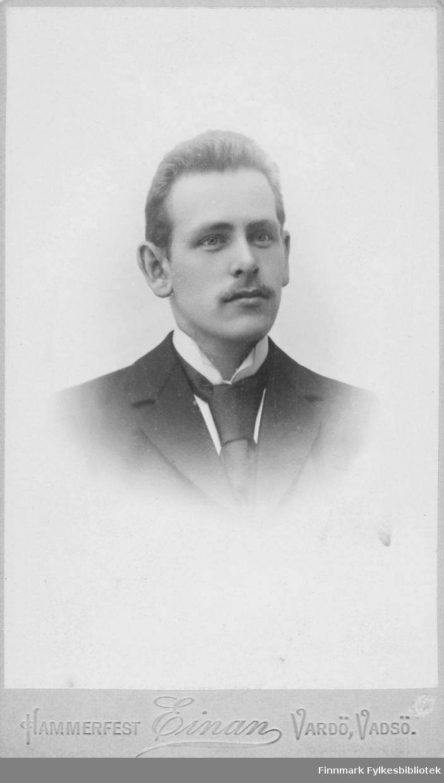 Portrett av ukjent ung mann. Han er kledt i mørk jakke og hvit skjorte. I halsen har han et mørkt slips. Han har bart